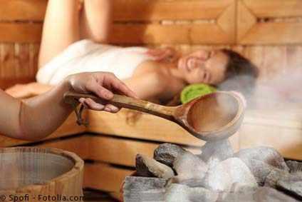 Frau mit Bademantel in Sauna